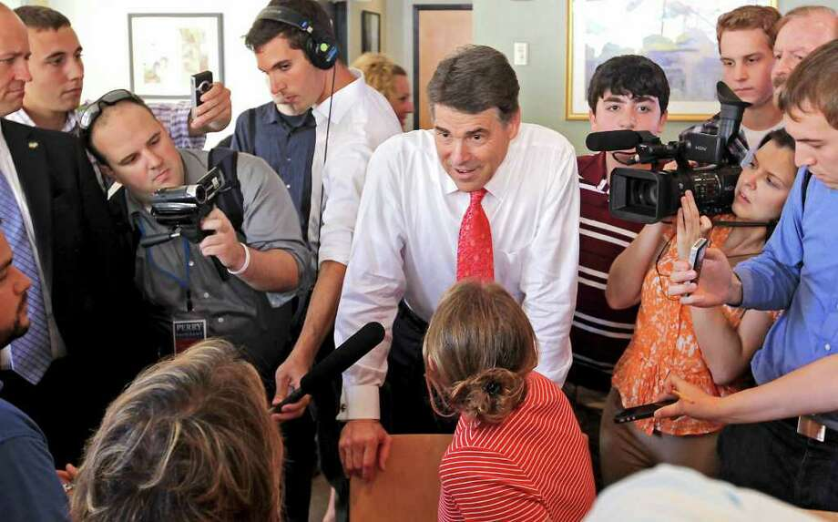 Republican presidential candidate, Texas Gov. Rick Perry talks with locals in a cafe during a visit to downtown Portsmouth, N.H., Thursday, Aug. 18, 2011. (AP Photo/Cheryl Senter) Photo: Cheryl Senter