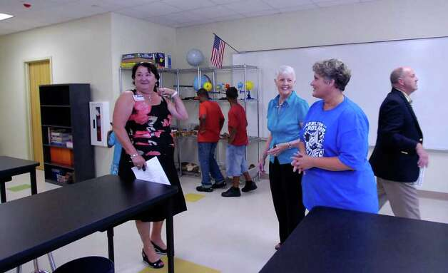 Science teacher Lisa Morrison, right, greets Patsy Magee, left, the Science Supervisor, and D'Ann Douglas, middle,  in the new science lab. Thursday was the grand opening of the Beaumont Independent School District's new school, Charlton-Pollard Elementary, which replaces Dunbar and Ogden elementary schools.  Dave Ryan/The Enterprise Photo: Dave Ryan
