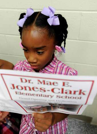 Third grader, Mackayla August looks over the program during the Grand Opening and Dedication ceremony at the new Mae Jones-Clark Elementary in Beaumont, Thursday. Tammy McKinley/The Enterprise Photo: TAMMY MCKINLEY