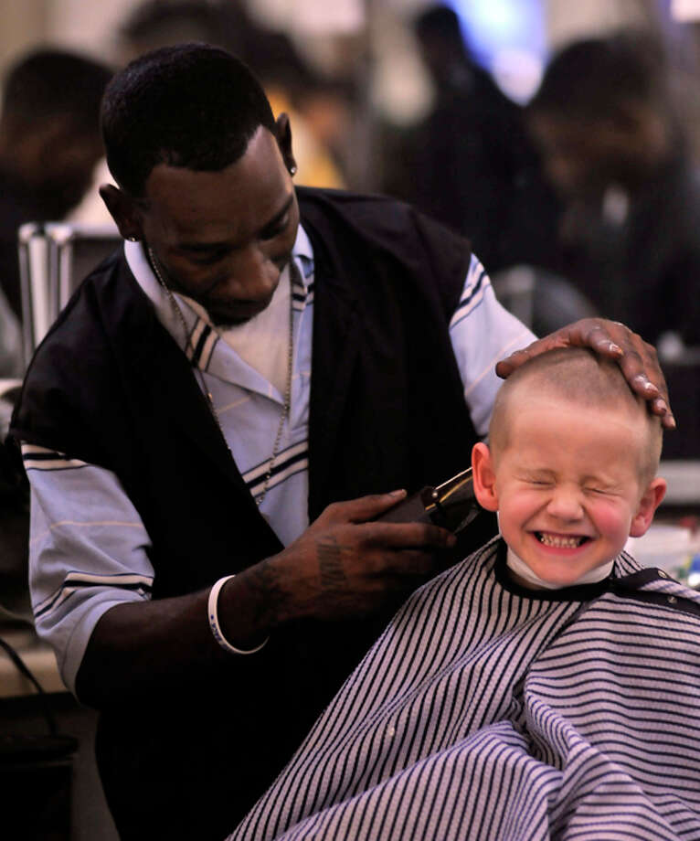 Jonathan Huseman giggles as Martell Gonzales cuts his hair during the annual free haircut event at Williams Barber College. It was sponsored by Williams in partnership with the Psi Alpha chapter of Omega Psi Phi. Photo: Robin Jerstad/Special To The Express-News