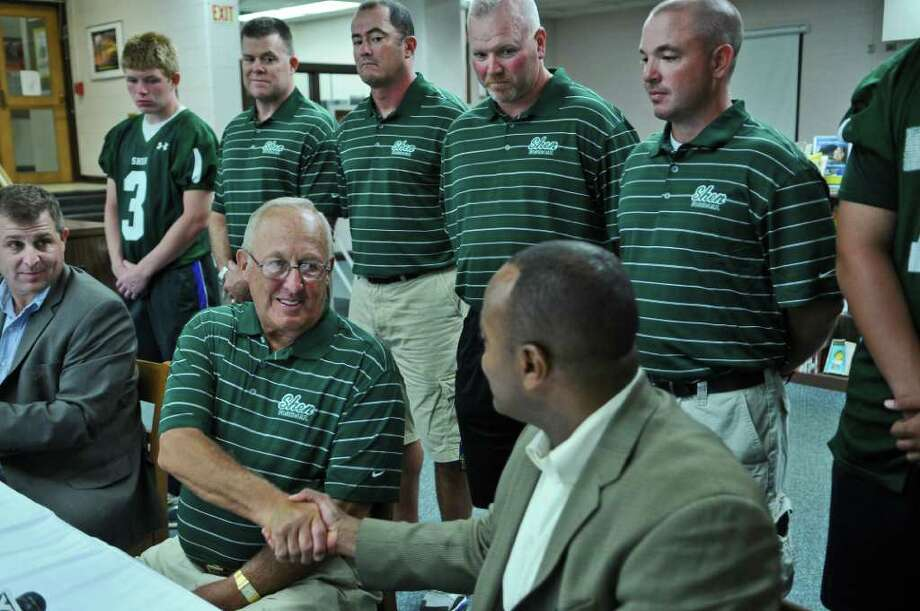 Shenendehowa High School football coach Brent Steuerwald, lower left, shakes hands with Superintendent Dr. Oliver Robinson, lower right, after Dr. Robinson spoke about the coach, during a press conference to announce his retirement after 33 years of coaching the team, on Thursday Aug. 18, 2011 in Clifton Park, NY. He started the football program at the school in 1968.  ( Philip Kamrass/ Times Union) Photo: Philip Kamrass / 00014304A