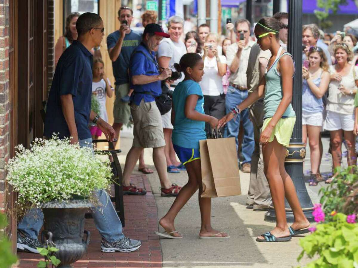 President Barack Obama, with his daughters Malia Obama, right, and Sasha Obama, center, leave the Bunch of Grapes book store in Vineyard Haven, Mass., Friday, Aug. 19, 2011, during a family vacation.