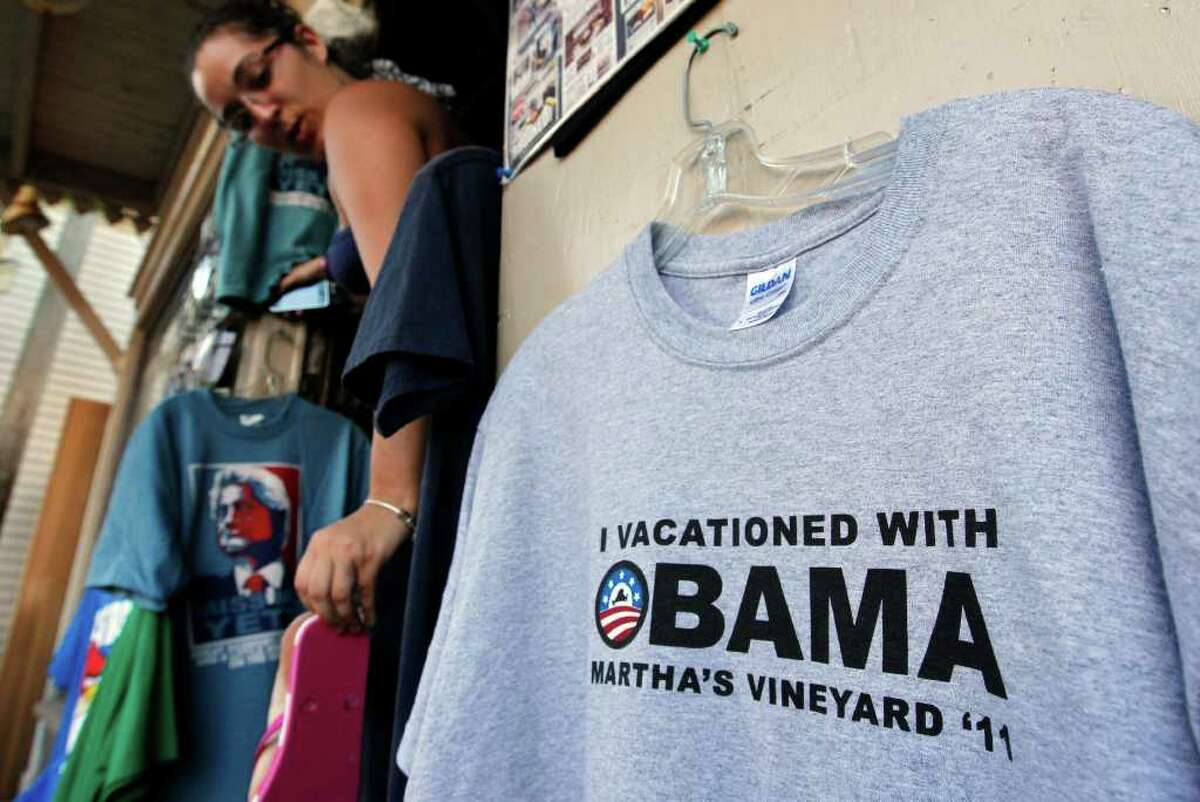 Rebecca Bourgeault of Lincoln, R.I., stops to adjust her shoe while departing a store in Oak Bluffs, Mass., Wednesday, Aug. 17, 2011, near a display featuring a shirt commemorating the anticipated visit of President Barack Obama to the island of Martha's Vineyard. Obama is expected to vacation on the island with his family during the last half of August 2011.