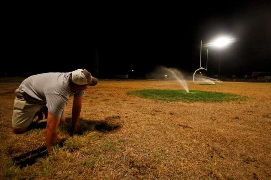 Aaron Hood, school superintendent and athletic director for Robert Lee High School in West Texas, adjusts the sprinkler that is life support for the school's bone-dry football field. Photo: Michael Paulsen, Chronicle