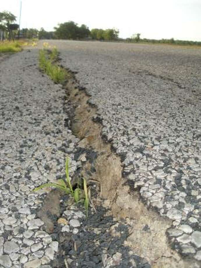 The drought has taken its toll on some of Fort Bend County's rural paved roads, including this one in the Cottonwood area near Needville. Photo: B.J. Pollock, For The Chronicle