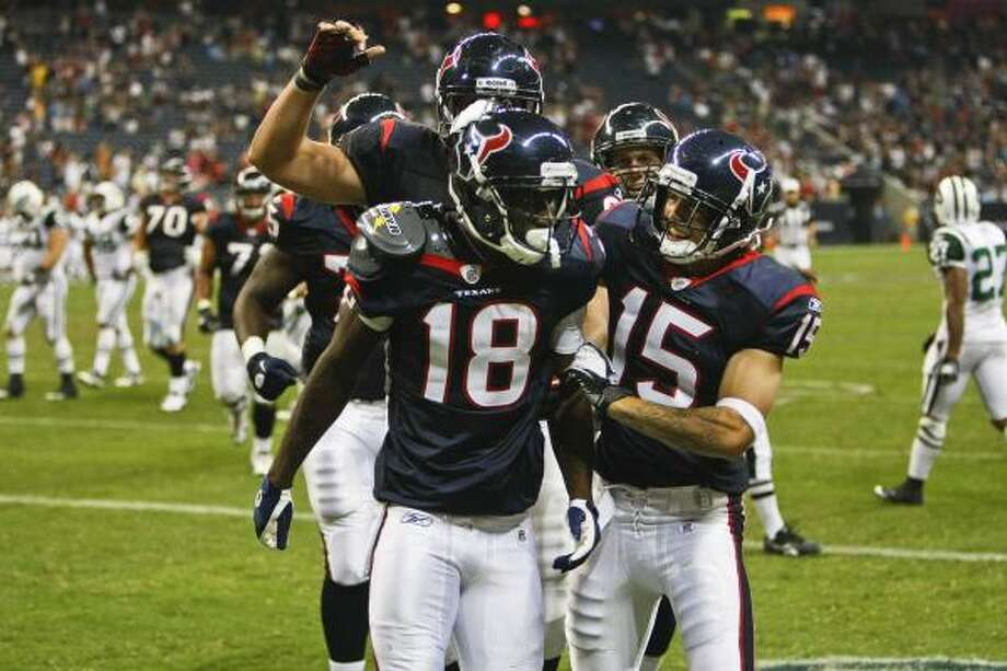 Lester Jean stands up and finds teammates mobbing him after his catch put the Texans on the goal line. Photo: Michael Paulsen, Chronicle