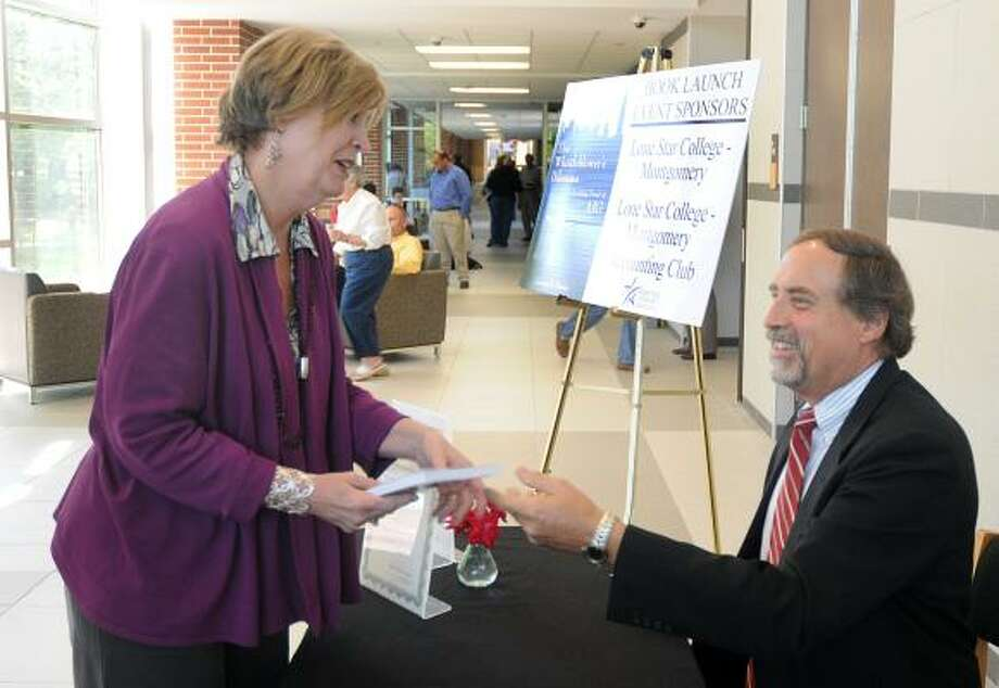DAVID HOPPER: FOR THE CHRONICLE MEET AND GREET: Mary Jo O'Neal, left, of The Woodlands, gets a signed copy of Gordon Massie's book The Whistleblower's Dilemma, Confronting Fraud at AIG, during a recent presentation and book signing sponsored by the Lone Star College-Montgomery Accounting Club and held in the music hall on campus. Photo: David Hopper, For The Chronicle