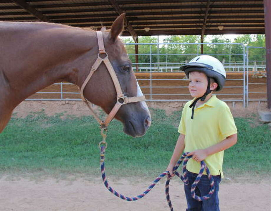 Paul leads Scarlet at Sienna Stables, a SIRE program site. Photo: Artdog-Houston