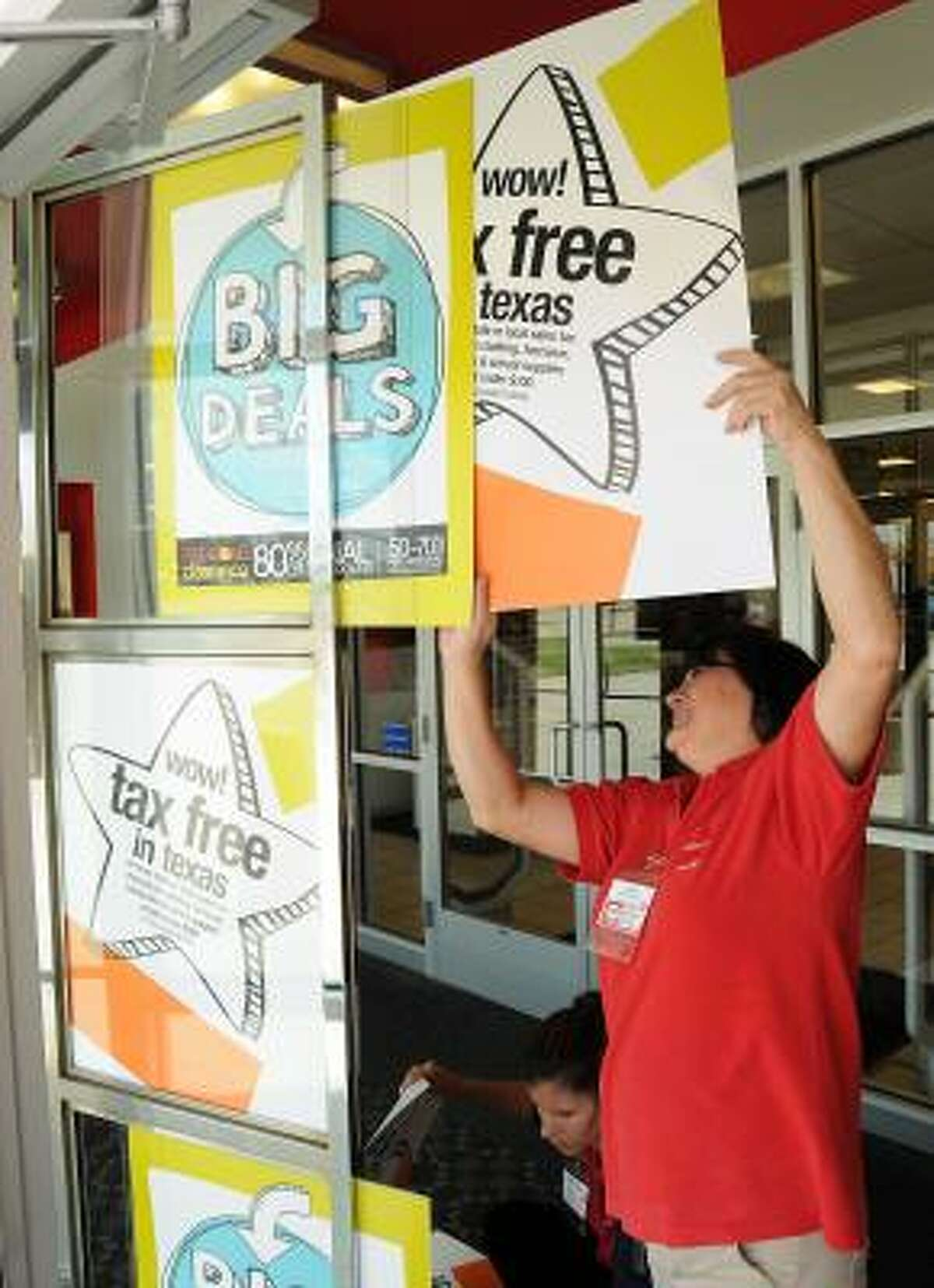 Fran Atchison posts a tax-free sign at the JC Penney in Katy.