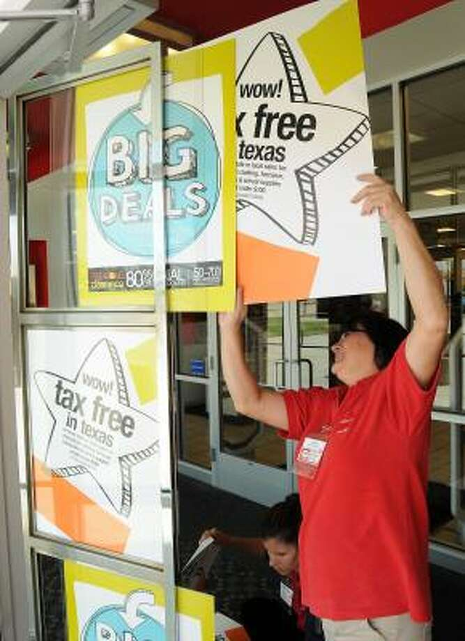 Fran Atchison posts a tax-free sign at the JC Penney in Katy. Photo: Dave Rossman, Chronicle