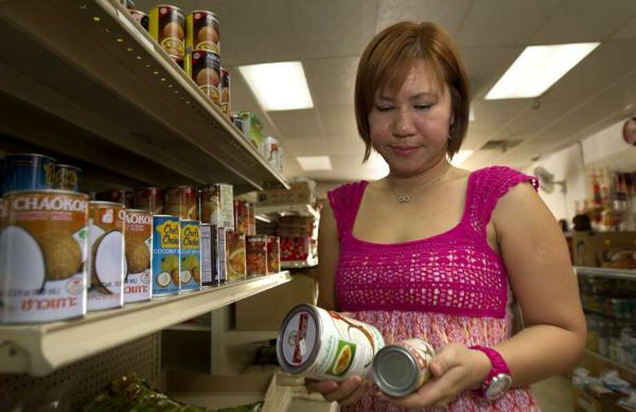 Noi Allen, owner of Asia Market, 1010 W. Cavalcade, looks over her store's supply of coconut milk. Depending on the brand, she'll pay up to $35 wholesale for a case of 13.5-ounce cans of coconut milk, twice what she paid six months ago. Photo: Cody Duty, Chronicle