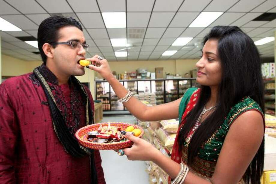 SWEET TRADITION: Mittal Chaudhari, 22, feeds sweets to her brother, Abhishek Chaudhari, 19, as part of a Hindu tradition, wishing him success in life. Photo: Suzanne Rehak, For The Chronicle