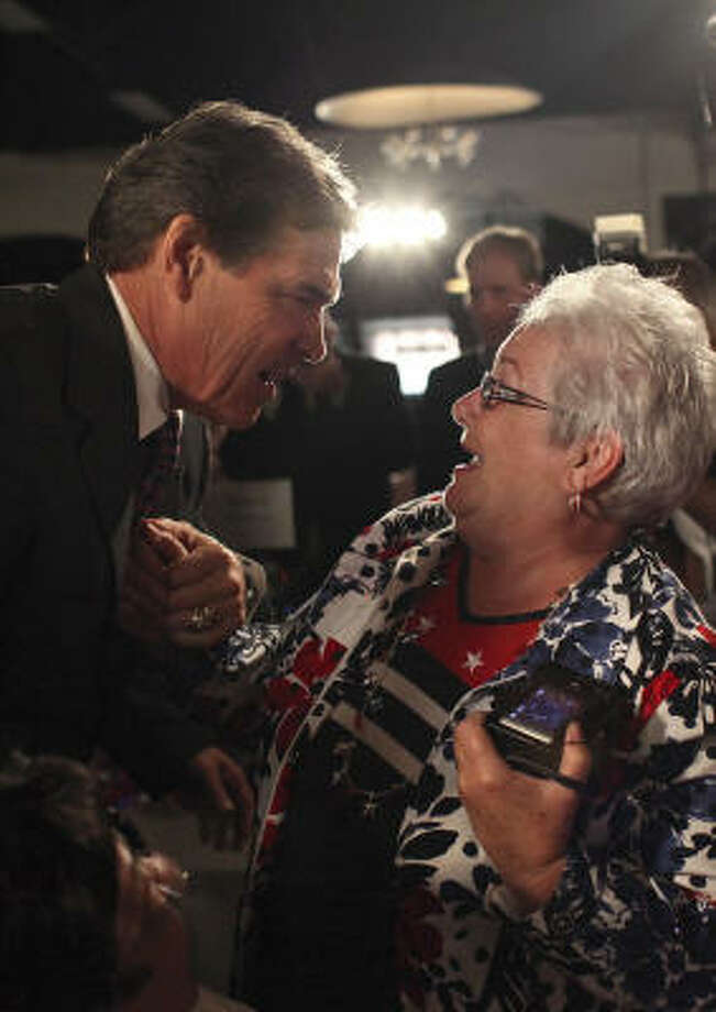 Linda Love, of Cedar Falls, Iowa, greets Gov. Rick Perry as he arrives for the Black Hawk County Lincoln Day Dinner. Photo: Lisa Krantz, San Antonio Express-News