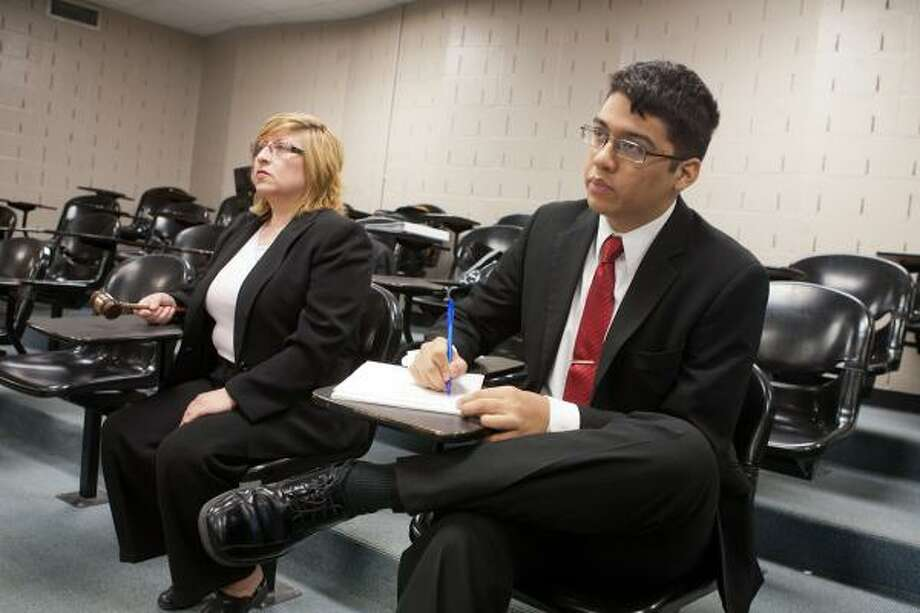 TEACHING OTHERS: Debate coach Victoria Beard and Silverio Ramirez critique a speech during a debate workshop at Spring Woods High School. Photo: R. Clayton McKee, For The Chronicle