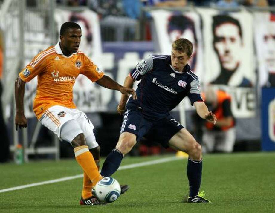 Zak Boggs of the New England Revolution tries to get the ball from Jermaine Taylor of the Houston Dynamo. Photo: Gail Oskin, Getty