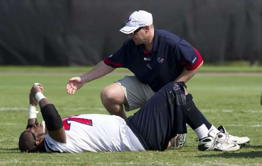Trainer Geoff Kaplan tends to Texans center Wade Smith. Smith went down during practice due to leg cramps. Photo: Brett Coomer, Chronicle