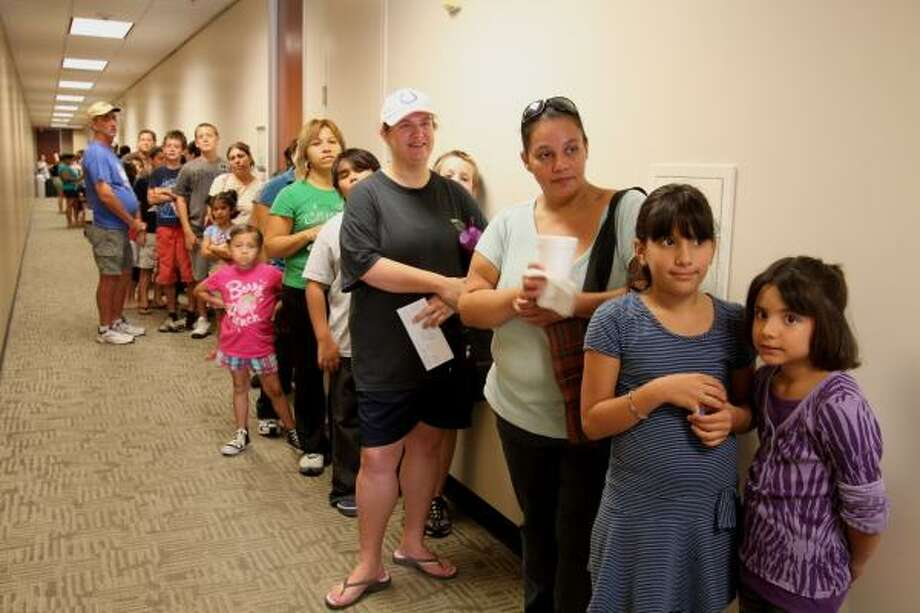 WORTH THE WAIT: Students and parents waited in line at Belhaven University, 15115 Park Row, before 8 a.m. Aug. 13 for free backpacks. In front are Brittany Castro, 7, Hemmenway Elementary second-grader; her sister, Alexis Castro, 9, Hemmenway Elementary fifth-grader, and their mom, Gina Castro. Photo: Suzanne Rehak, For The Chronicle