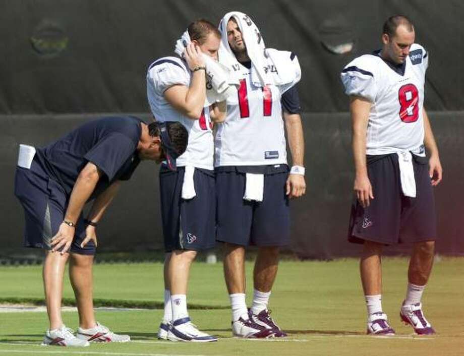 Texans quarterbacks coach Greg Knapp takes a break in practice with quarterbacks T.J. Yates (13), Matt Leinart (11) and Matt Schaub (8). Photo: Brett Coomer, Houston Chronicle