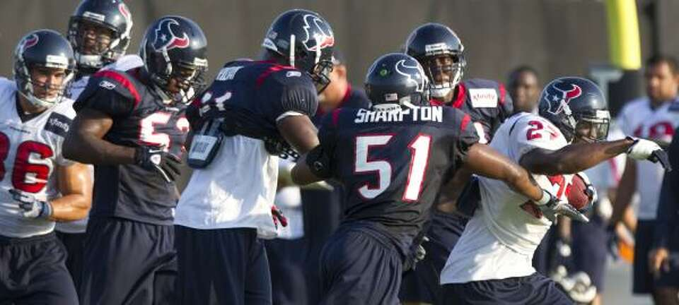 Texans running back Chris Ogbonnaya, far right, runs the ball past a host of defenders.