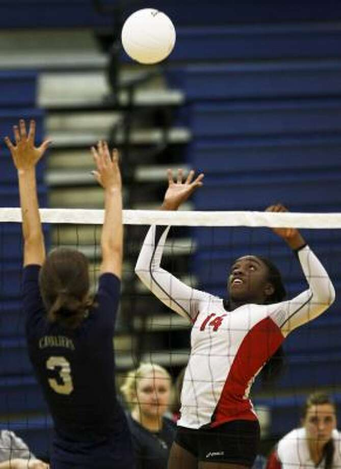 Olivia Ogwumike (14) of Cypress Woods goes up for a spike as Taylor Erwin tries to block it Tuesday night. Photo: Michael Paulsen, Chronicle