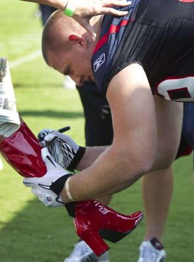 Texans defensive end J.J. Watt autographs a boot. Photo: Brett Coomer, Chronicle