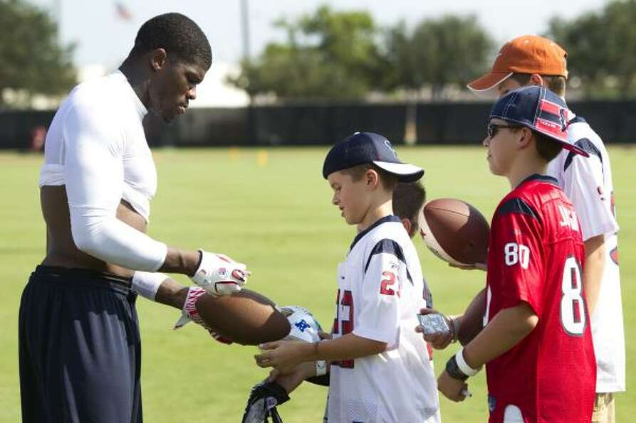 Texans wide receiver Andre Johnson signs autographs at the end of practice.