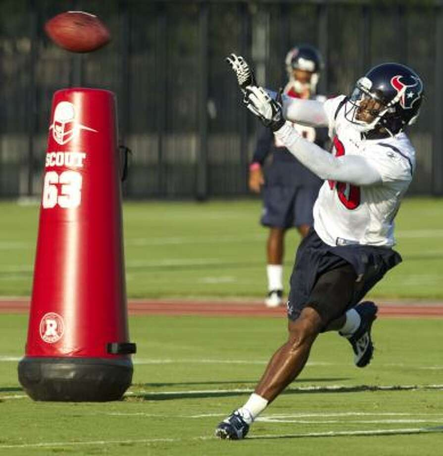 Texans wide receiver Andre Johnson runs past a blocking dummy to catch a ball. Photo: Brett Coomer, Chronicle