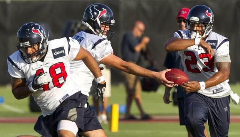 Texans fullback Zach Pauga leads the way as quarterback Matt Schaub hands the ball off to running back Arian Foster. Photo: Brett Coomer, Chronicle