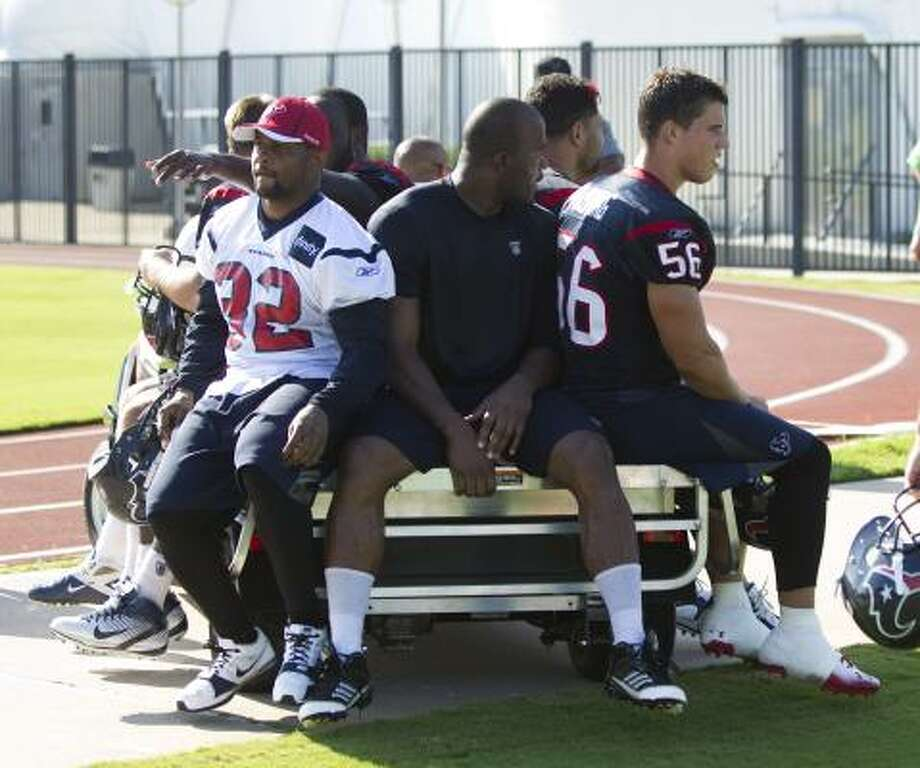 Texans players ride away from practice on a cart. Photo: Brett Coomer, Chronicle