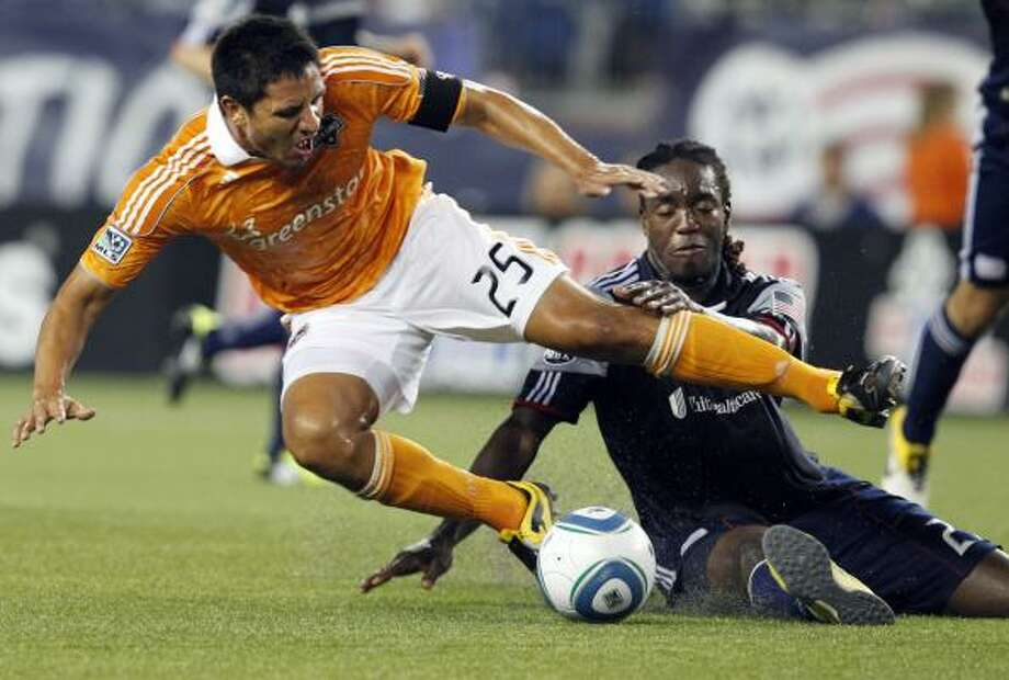 Dynamo forward Brian Ching is upended on a challenge by New England Revolution midfielder Shalrie Joseph, right. Photo: Elise Amendola, Associated Press