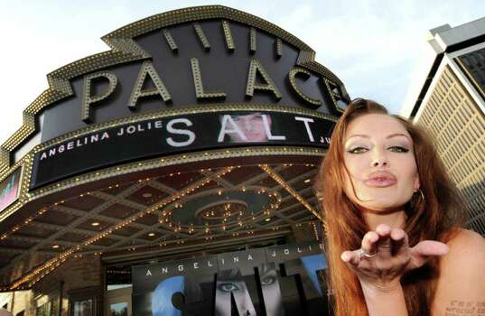 "Tiffany Claus, who works as an ""Angelina Jolie Look-a-Like"", blows a kiss outside the Palace Theatre as movie goers file into the venue for the Albany Premiere of the movie ""Salt"", on Thursday, July 22, 2010, in Albany, NY.  Complimentary tickets were passed out to the public to be among the first to see the Columbia Pictures' action film as a thank you to the hundreds of local residents and businesses who cooperated with the production company while they were on location in Albany for portions of the film.  Claus who embarked on her career as an Angelina Jolie impersonator when she was discovered on Facebook by Tira Banks, worked the crowd courtesy of Yono's & dp An American Brasserie.  Photos for Daily news coverage.    (Luanne M. Ferris / Times Union) Photo: LMF, AP Photo / 00009465A"