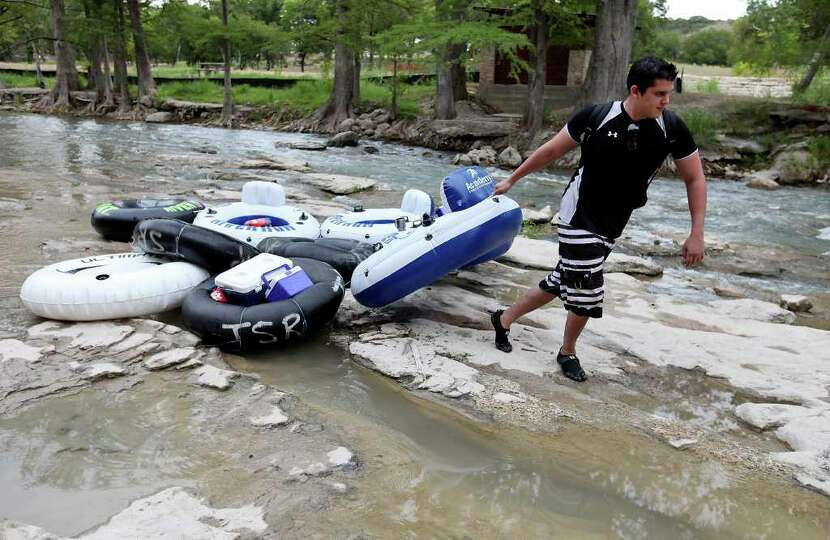 Graham Johnson drags his groups tubes on a low section of the Guadalupe River horseshoe after a floa