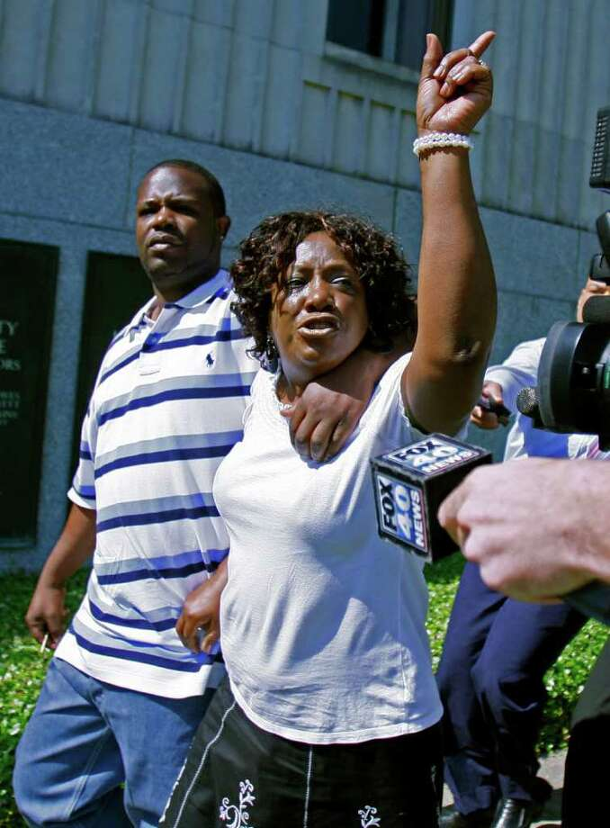 """FILE - In this Aug. 16, 2011 file photo, Ablene Cooper, a woman who works for the brother of author Kathryn Stockett, and her son Antonio Cooper,  leave the Hinds County Courthouse in Jackson, Miss., expressesing her disappointment that a circuit judge dismissed her lawsuit against the author of """"The Help"""" because a statute of limitations issue. Cooper wants a judge to reinstate a lawsuit that claims Kathryn Stockett, author of the bestselling novel-turned-move """"The Help,"""" used her likeness without permission. (AP Photo/Rogelio V. Solis, file) Photo: Rogelio V. Solis"""