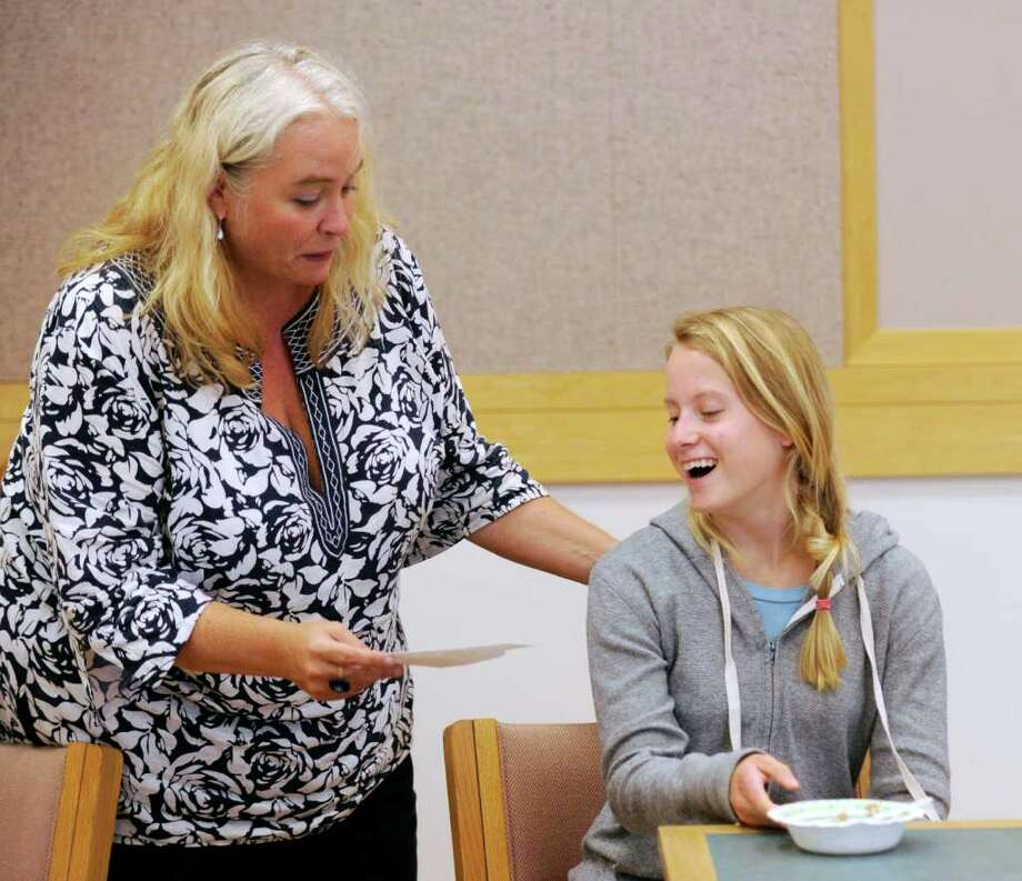 Greenwich Teen Services Librarian Margaret Walsh, left, gives a prize of two iTunes gift cards to Catherine Colbert, 17, of Greenwich, during an end of summer party to celebrate the summer reading done those who participated in the Teen Summer Reading program offered by the library, at Greenwich Library, Friday afternoon, Aug. 19, 2011. Photo: Bob Luckey / Greenwich Time