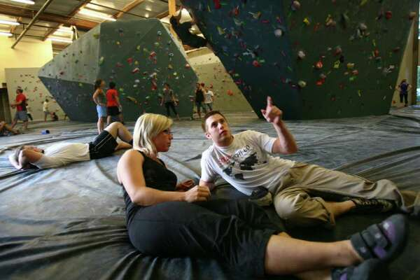 Andrea Erdahl and Cameron Bloomer talk about a route at the Seattle Bouldering Project on Wednesday, August 17, 2011. The Seattle Bouldering Project is an indoor climbing gym. Ropes are not used at the gym and climbers that fall land on a thick pad on the floor.