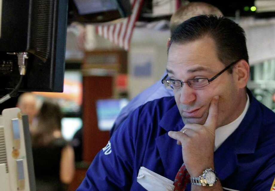 A specilaist works at his on the floor of post the New York Stock Exchange, Friday Aug. 19, 2011. (AP Photo/Richard Drew) Photo: Richard Drew