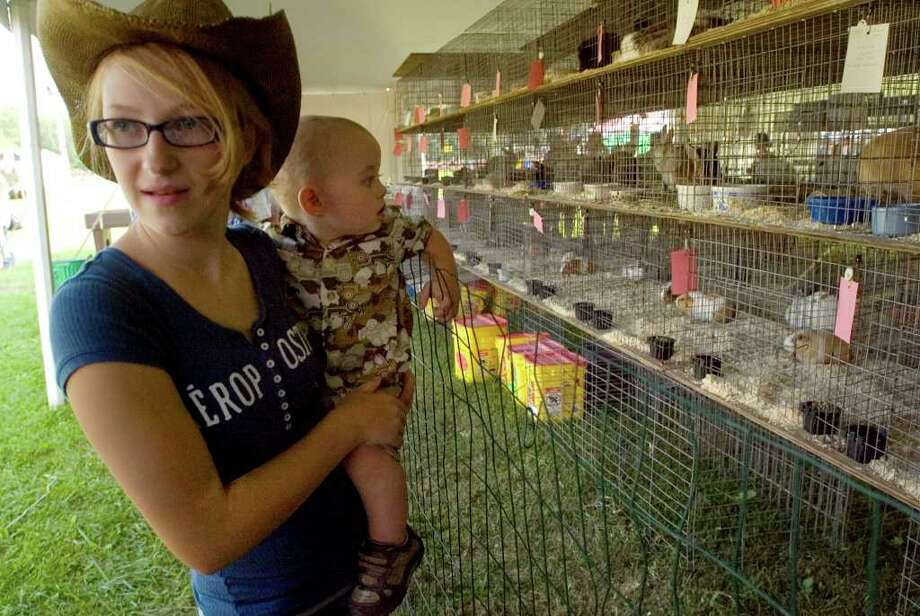 Dallas Miller, 14, of Roxbury, shows her cousin D.J. Hammer, 1, of New Milford, the rabbit exhibit during the first evening of the 60th Bridgewater Country Fair on Friday, Aug. 19, 2011. Photo: Jason Rearick / The News-Times