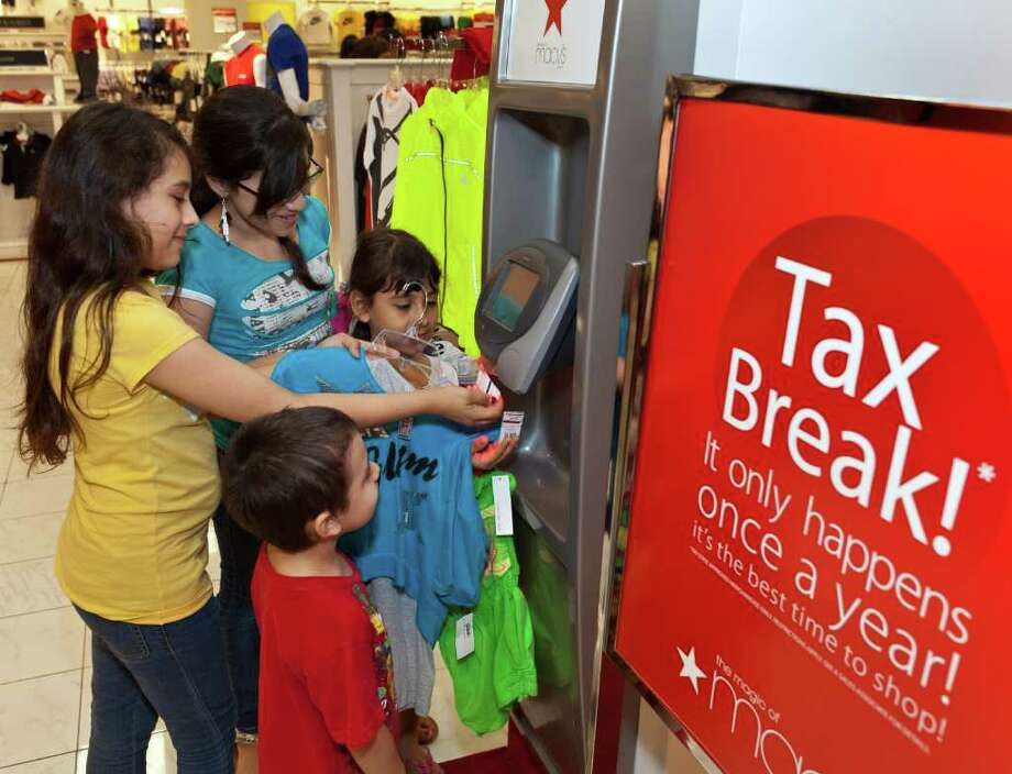 Shoppers take advantage of the sales tax holiday on Friday, Saturday and Sunday at Macy's in Memorial City Mall, 303 Memorial City Way. ID: kids checking prices at the scanner kiosk are 10-year-old Jazmin Arzate (in yellow); Jennifer Arzate, age 12 (in blue); Jatziri Arzate, age 7 (in pink, face behind hanger) and Fidel Arzate, age 3 (in red). Friday, August 19, 2011. (Craig H. Hartley/Chronicle) Photo: Craig Hartley, Freelance / Copyright: Craig H. Hartley