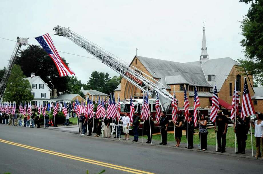 Area residents and members of the Patriot Guard hold flags outside the funeral for U.S. Navy SEAL Brian Bill at St. Cecilia Parish in Stamford on Friday, August 19, 2011. Photo: Lindsay Niegelberg / Stamford Advocate