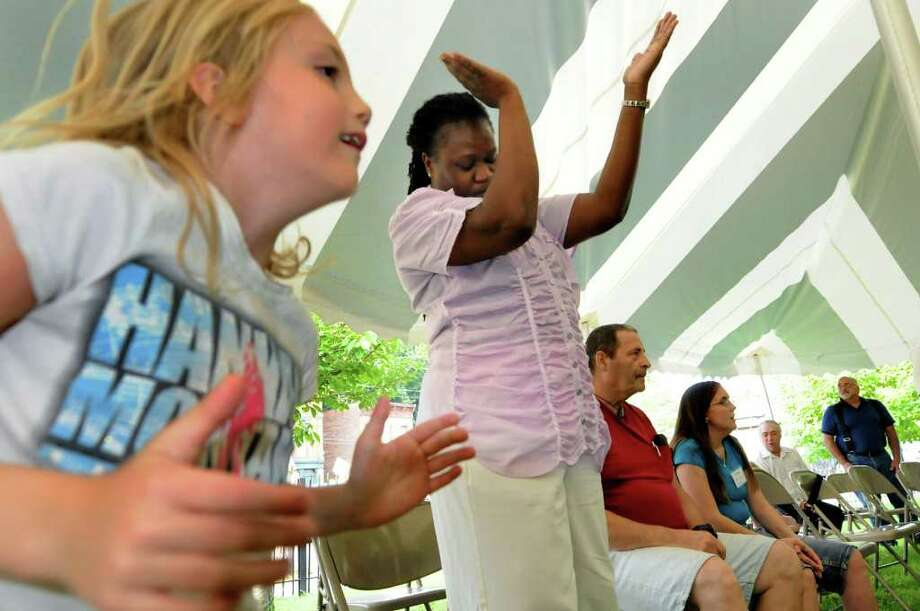 Angel Bryan, 7, left, and Pauline Glenn celebrate the music of Wave Ministry during an outdoor tent revival on Friday, Aug. 19, 2011, at Mount Ida Community Baptist Church in Troy, N.Y. (Cindy Schultz / Times Union) Photo: Cindy Schultz