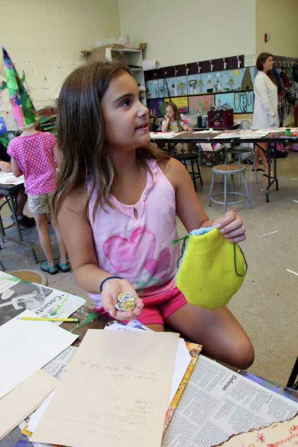 Marisa Damiano, age 9 of Troy, left, shows off an art project that she made at the Arts Center of the Capital Region, Troy, in a class called, Wizards, Wands and Magic on Thursday, Aug. 11, 2011. The class is offered during a summer camp where some students benefit from the Hope Fund. (Erin Colligan / Special To The Times Union)