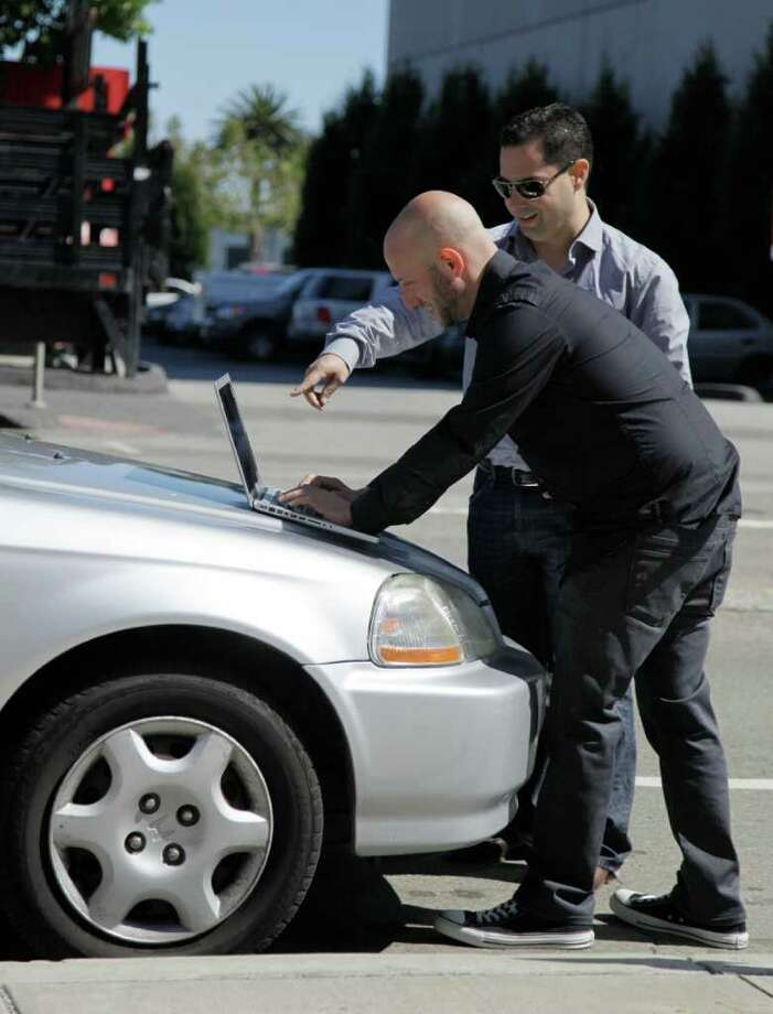 In this photo taken Tuesday Aug. 16, 2011, security consultants Don Bailey, rear, and Mathew Solnik with iSEC Partners, demonstrate with a computer how they force cars with certain alarm systems to unlock their doors and start their engines by sending them text messages in San Francisco. (AP Photo/Eric Risberg) Photo: Eric Risberg