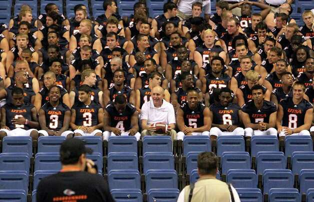 UTSA football players join head coach Larry Coker (center) for a team photo during Media Day for the UTSA football program at the Alamodome on Friday, August 19, 2011. Kin Man Hui/kmhui@express-news.net Photo: KIN MAN HUI, Express-News / San Antonio Express-News