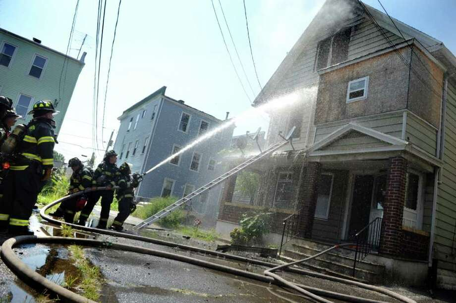 Firefighters work to put out a structure fire on Madison Court in Bridgeport, Conn. Saturday, Aug. 20, 2011. Photo: Autumn Driscoll / Connecticut Post