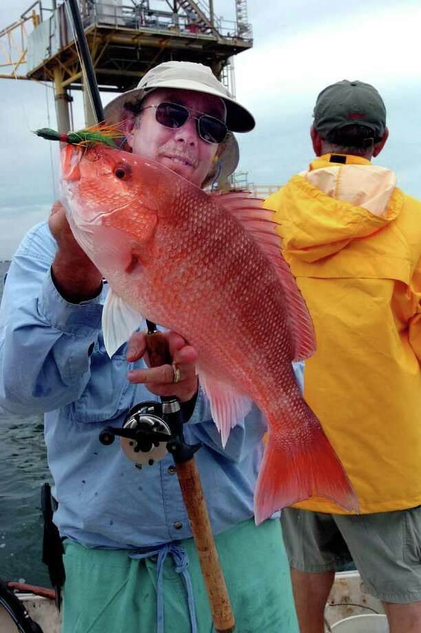 Joe Richard of Gainesville, Florida admireS a red snapper he caught in the Gulf of Mexico fishing about 40 miles out of Sabine Pass. Pete Churton/The Enterprise / Beaumont