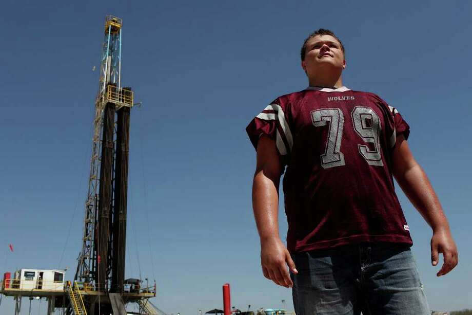 Metro - Riley Mathews, 17, a left tackle and defensive back at Dilley High School, stands on his cousin's land where drilling is occurring on Wednesday, August 17, 2011. LISA KRANTZ/lkrantz@express-news.net Photo: LISA KRANTZ, Express-News / SAN ANTONIO EXPRESS-NEWS