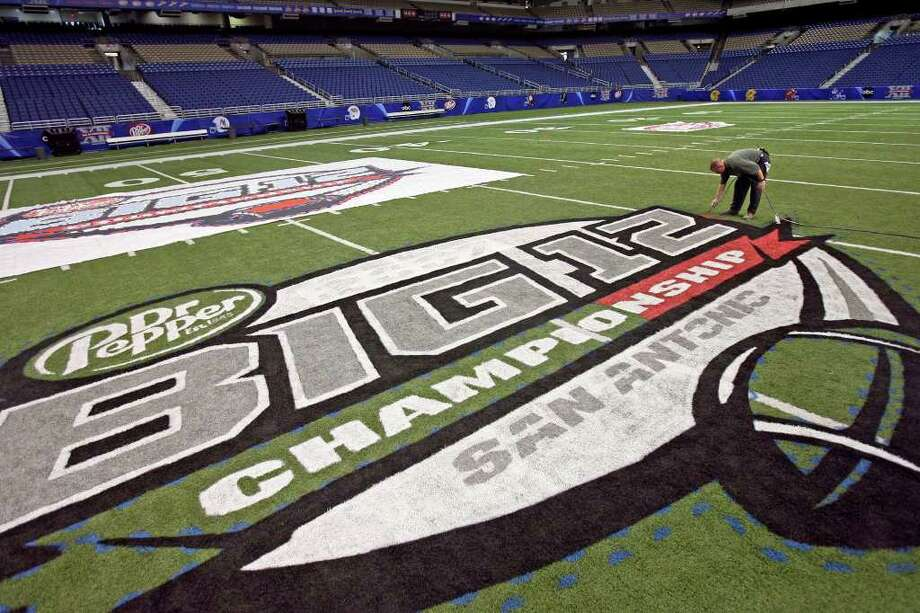 Sports    The Big 12 logo is colored by painter Tom McAfee Thursday afternoon at the Alamodome in preparation for this weekend's championship game.  Big 12 Conference Championship logo painted on the Alamodome floor by Tom McAffee  Tom Reel/Staff  November 29, 2007 Photo: TOM REEL, Express-News / SAN ANTONIO EXPRESS-NEWS