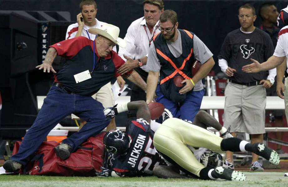 Former Oilers head coach Bum Phillips, left, is knocked to the ground as a play goes out of bounds during the second quarter on Saturday night. Photo: Brett Coomer, Houston Chronicle / © 2011 Houston Chronicle