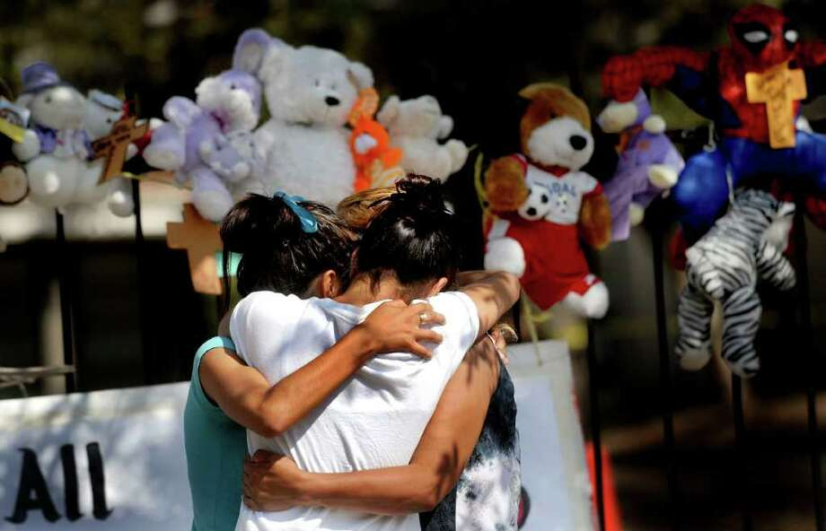 The family of Rudy Alejos, 6, gather at the entrance of the Summerview Apartments on Saturday, Aug. 20, 2011. The child's body was found on Saturday in the rubble of a fire that broke out late Tuesday, destroying two buildings, and displacing over 70 people. Photo: BILLY CALZADA, Express-News / gcalzada@express-news.net