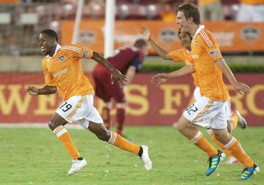 Dynamo midfielder Alex Dixon (19) celebrates along with teammate Bobby Boswell (32) after scoring the winning goal on Saturday night. (AP Photo/Patric Schneider) Photo: Patric Schneider, Associated Press / AP